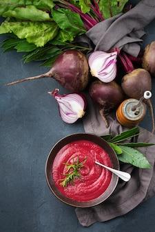 Saisonale herbst-herbst-gemüse cremige rote-bete-suppe mit zutaten auf einem küchentisch.