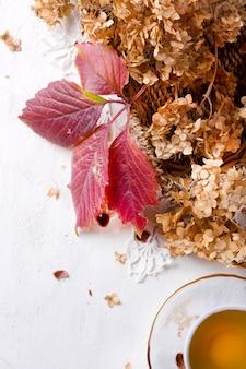Saisonale herbstdekoration für zuhause, mit tee, vintage-teeservice, hortensie, weidenkorb und kürbis.