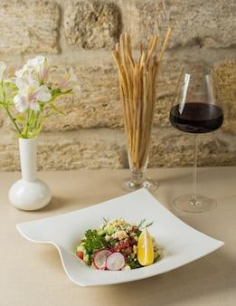 Saisonaler blumenkohlsalat mit einem glas burgunder