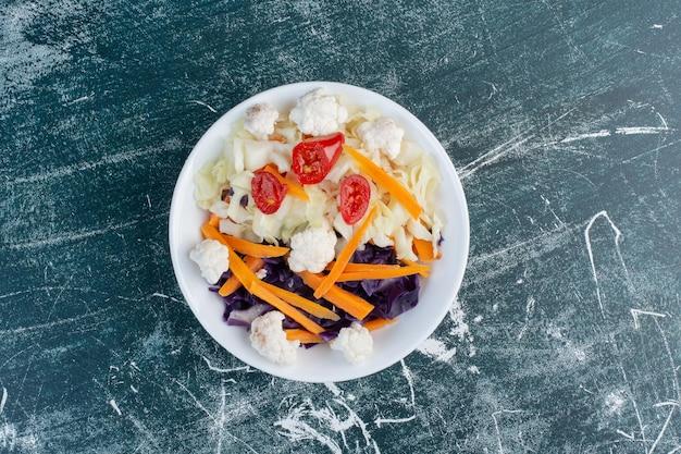 Saisonaler gemüsesalat mit gehackten karotten und blumenkohl.