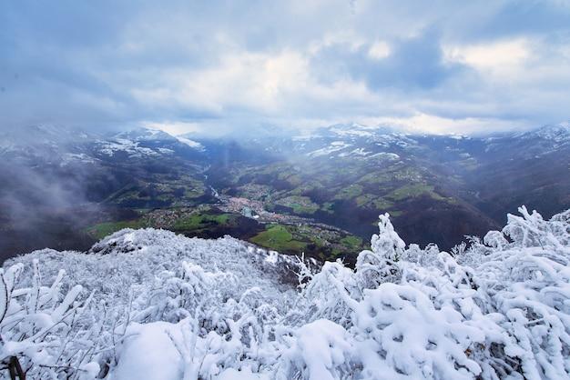 Saisonaler kontrast mit schnee auf den bäumen blick auf das dorf im unteren tal mit wiesen