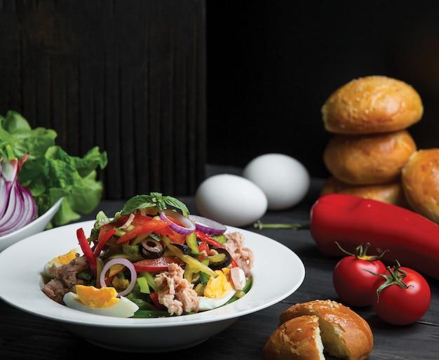 Saisonaler salat mit oliven, eiern und zwiebeln