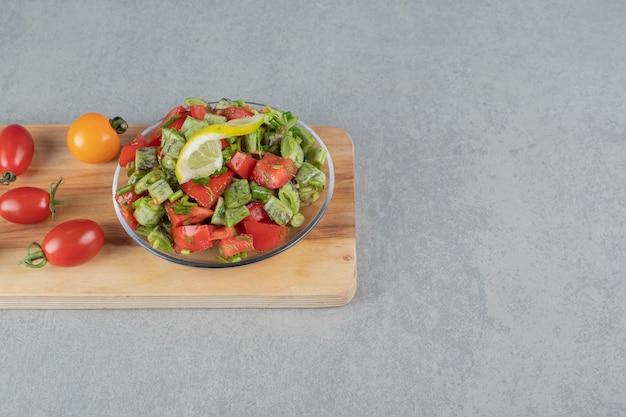 Saisonaler salat mit roten kirschtomaten und grünen bohnen.