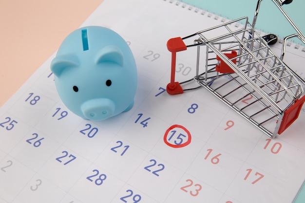Saisonaler verkauf. sparschwein mit kalender, supermarktwagen auf einem bunten hintergrund.