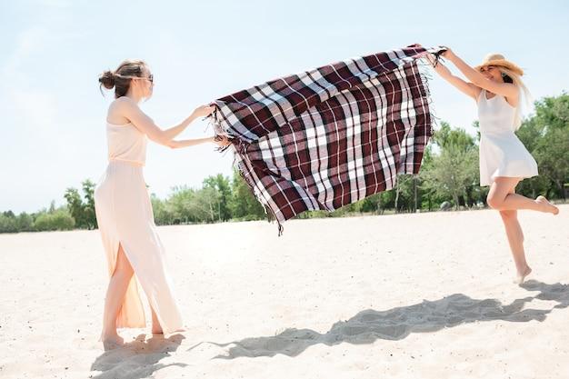 Saisonales fest im strandresort glückliche mädchenfreunde, die sich ausruhen und spaß am strand haben?