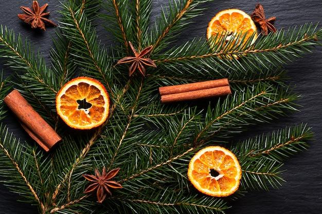 Saisonales hintergrundkonzept winter- oder weihnachtsgewürze und kiefer verlassen auf schwarzem schiefersteinbrett mit kopienraum