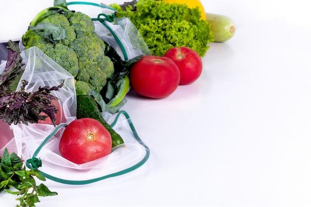 Saisonales obst und gemüse auf weiß. rohe bio-frischwaren vom markt. null abfall einkaufen. wiederverwendbare einkaufstüten