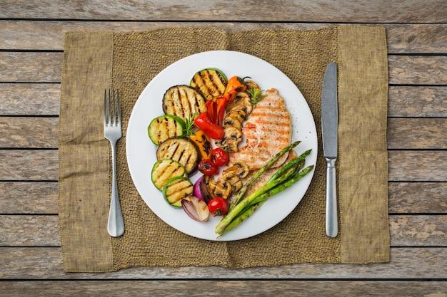 Saisonales, sommerliches essenskonzept. gegrilltes gemüse und hähnchenbrust in einem teller auf einem holztisch. draufsicht flach legen hintergrund