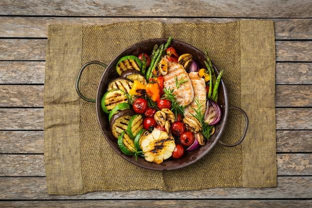Saisonales, sommerliches essenskonzept. gegrilltes gemüse und hühnerbrust in einer pfanne auf einem holztisch. draufsicht flach legen hintergrund