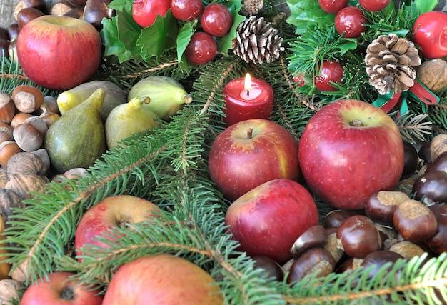 Saisonfrüchte in der weihnachtsdekoration und in den kerzen