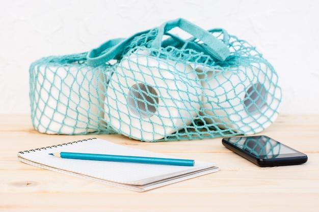 Saitentasche mit toilettenpapierrollen und notizbuch mit bleistift