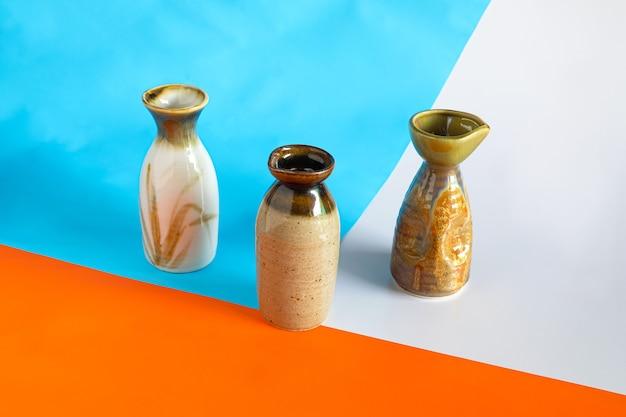 Sake-flasche auf geometrischem frühlingsfarbhintergrund.