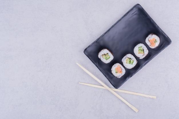Sake maki brötchen mit lachs und avocado in schwarzer platte.