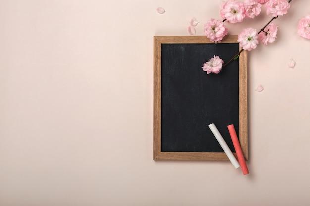 Sakura blüht mit kreidebrett auf einem pastellrosahintergrund