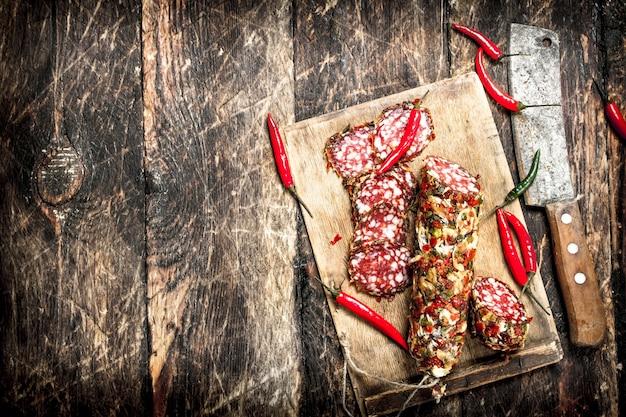 Salalmi mit scharfen chilischoten auf dem brett auf einem hölzernen hintergrund