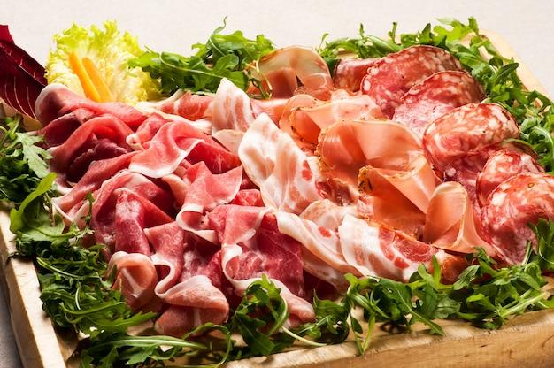 Salami aufschnitt in box mit grünen umgeben