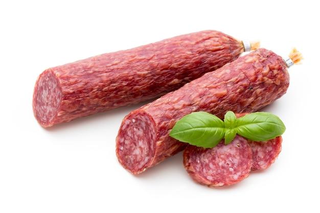 Salami geräucherte wurst, basilikumblätter und pfefferkörner isoliert