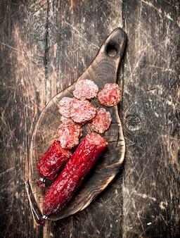 Salami mit kräutern und gewürzen auf einem brett auf einem hölzernen hintergrund