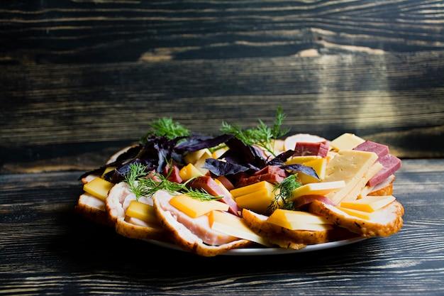 Salami, schinken-käse-salat und gemüse pressen von wurst und wurstwaren auf einem festlichen tisch