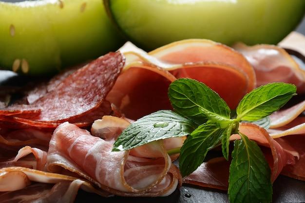 Salami, schinken, speck, serviert mit melone und minze auf dem schneidebrett. italienisches mittagessen