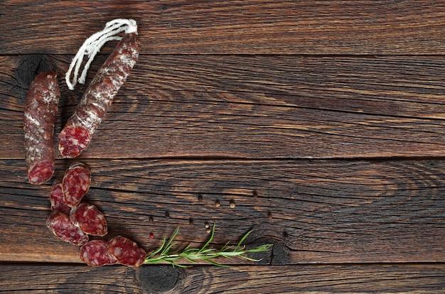 Salami-würstchen in scheiben geschnitten mit pfeffer und rosmarin