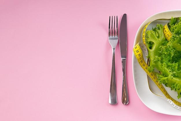 Salat auf dem teller mit lineal um ihn herum, während gabel mit messer in der nähe und alles auf dem rosa hintergrund liegend,
