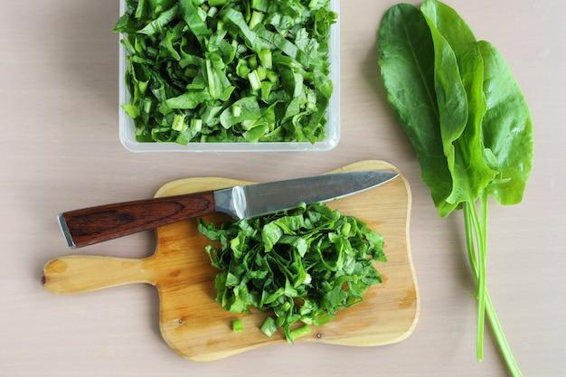 Salat auf schneidebrett geschnitten und messer auf tisch