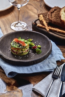 Salat aus avocado, meeresfrüchten, fleisch, gemüse und kürbiskernen. diätetisch, gesund und lecker. festliche bankettgerichte. speisekarte des gourmetrestaurants. weißer hintergrund.