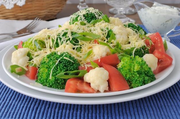 Salat aus blumenkohl und brokkoli, tomaten und käse