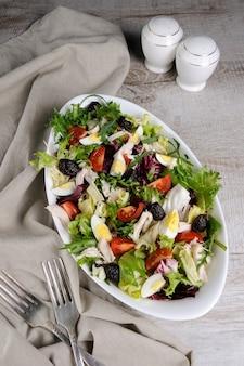 Salat aus der mischung aus salatblättern mit tomaten eier hähnchenbrustscheiben und getrockneten oliven