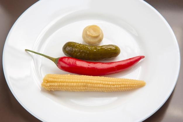 Salat aus eingemachten und eingelegten pilzen, gurken und rotem pfeffer auf einem weißen teller. essen und gemüse. diät und gewichtsverlust