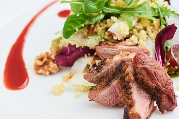 Salat aus entenbrust, daikon, trauben und couscous serviert auf einem weißen teller