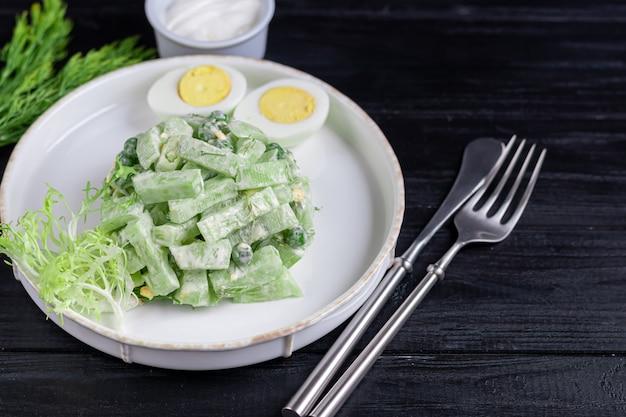 Salat aus frischen gurken, spinatblättern, rucola, avocado. serviert mit eierscheiben und rotem pfeffer.