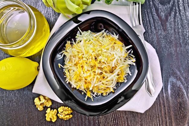 Salat aus frischen karotten, kohlrabi und walnüssen, gewürzt mit honig und zitronensaft in einem teller auf einer serviette auf holzbretthintergrund oben