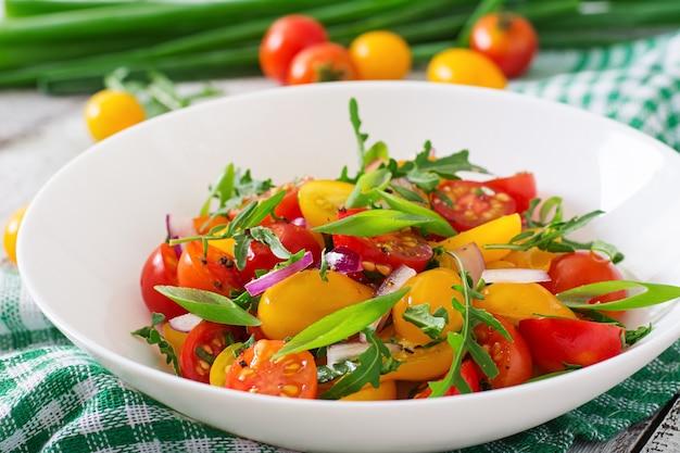Salat aus frischen kirschtomaten mit zwiebeln und rucola