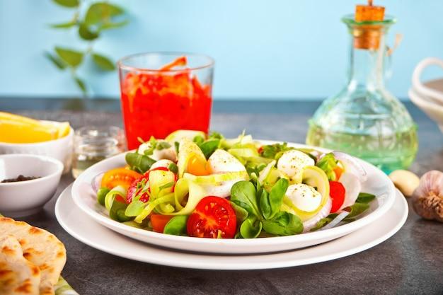 Salat aus frischen kirschtomaten, mozzarella, basilikum, rettich und anderem grün auf dem esstisch