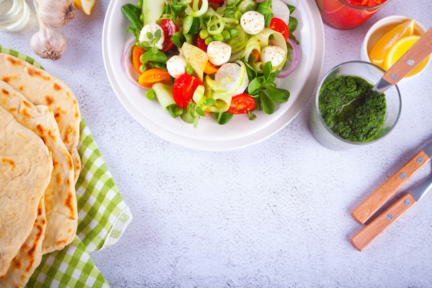 Salat aus frischen kirschtomaten, mozzarella, basilikum und anderem gemüse auf dem esstisch mit fladenbrot