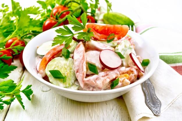 Salat aus frischen tomaten, gurken und rettich mit frühlingszwiebeln und petersilie, gewürzt mit mayonnaise und sauerrahm in einer schüssel, handtuch und gabel auf holzbretthintergrund