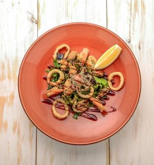 Salat aus gebratenen meeresfrüchten mit frischem gemüse