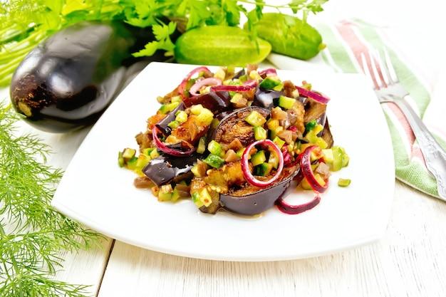 Salat aus gebratener aubergine, frischer und eingelegter gurke mit roten zwiebeln, gewürzt mit pflanzenöl und würziger sauce in einem teller, serviette, gabel und dill auf einem holzbretthintergrund