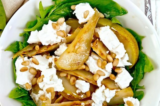 Salat aus gebratener birne, spinat, gesalzenem feta-käse und zedernnüssen in einem teller auf einer serviette gegen ein helles holzbrett oben