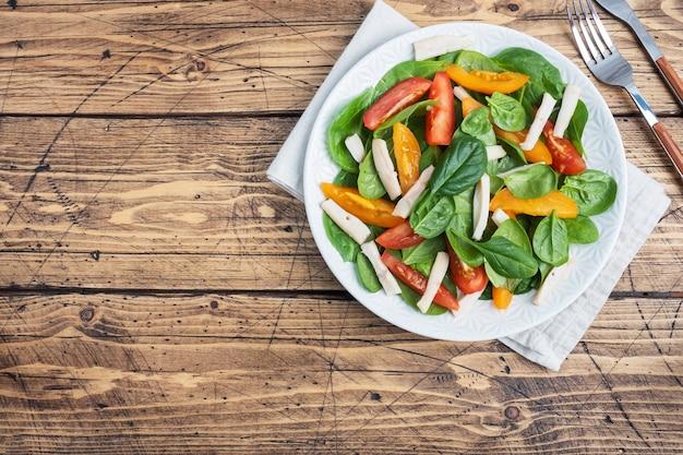 Salat aus gekochtem tintenfisch, frischen tomaten, spinatblättern. köstliches helles diätgericht mit gemüse und meeresfrüchten. kopieren sie die draufsicht des raums
