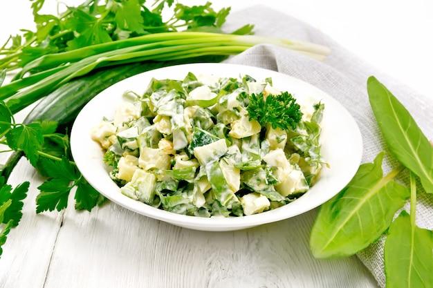 Salat aus gurke, sauerampfer, salzkartoffeln, eiern und kräutern, gekleidet mit mayonnaise in weißem teller, petersilie, frühlingszwiebeln und serviette auf holzbretthintergrund Premium Fotos