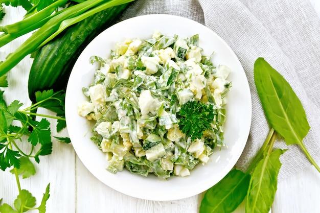 Salat aus gurke, sauerampfer, salzkartoffeln, eiern und kräutern, gekleidet mit mayonnaise