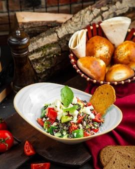 Salat aus gurken und tomaten mit käse und gemüse mischen
