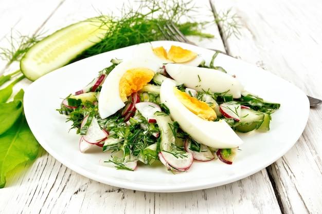 Salat aus radieschen, gurken, sauerampfer, gemüse und eiern, gekleidet mit mayonnaise und sauerrahm in einem teller auf dem hintergrund von hellen holzbrettern