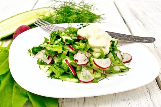 Salat aus rettich, gurke, sauerampfer und grün, gekleidet mit mayonnaise in einem weißen teller auf dem hintergrund des holzbretts