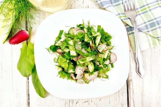 Salat aus rettich, gurke, sauerampfer und grün, mit pflanzenöl in einem teller auf einem hintergrund aus hellem holzbrett angerichtet