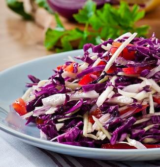 Salat aus rot- und weißkohl und süßem rotem pfeffer, gewürzt mit zitronensaft und olivenöl in holzschale