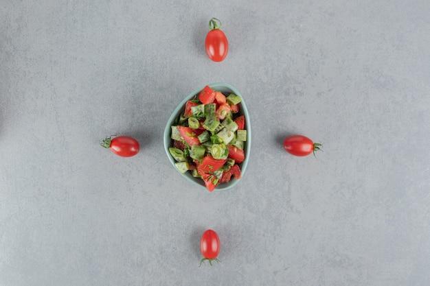 Salat aus roten kirschtomaten und bohnen in einer blauen tasse